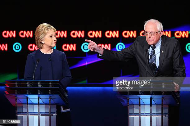 /Democratic presidential candidate Senator Bernie Sanders speaks as Democratic presidential candidate Hillary Clinton looks on during the CNN...
