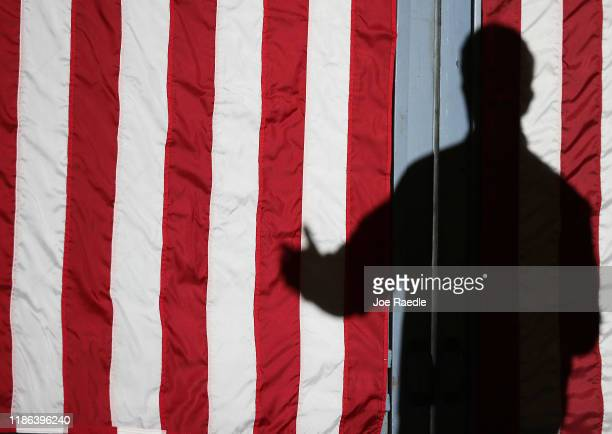 Democratic presidential candidate South Bend, Indiana Mayor Pete Buttigieg cast a shadow on the American flag as he speaks during a barn party town...