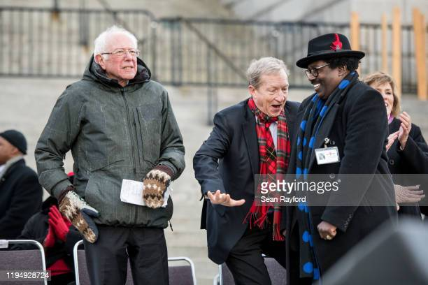 Democratic presidential candidate Tom Steyer center dances with a man as fellow Democratic presidential candidate Sen Bernie Sanders looks out over...