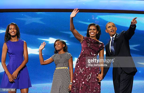 Democratic presidential candidate US President Barack Obama stands on stage with First lady Michelle Obama and Sasha Obama and Malia Obama after...
