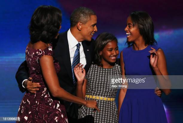 Democratic presidential candidate US President Barack Obama stands on stage with his family First lady Michelle Obama Sasha Obama and Malia Obama...