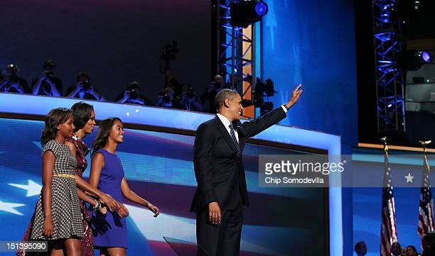 Democratic presidential candidate US President Barack Obama waves on stage after accepting the nomination with his family Sasha Obama First lady...
