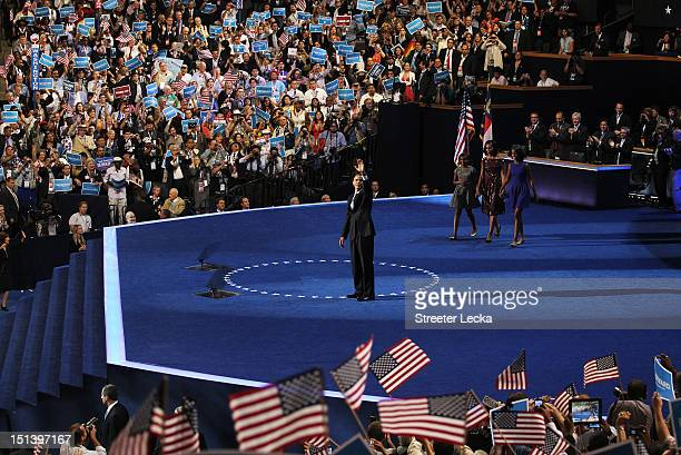 Democratic presidential candidate US President Barack Obama waves on stage after accepting the nomination with his family Malia Obama Sasha Obama and...
