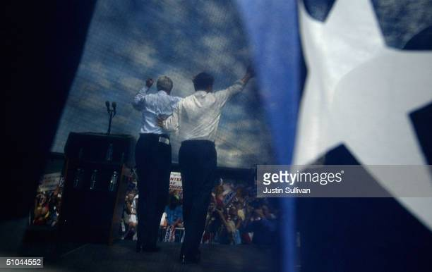 Democratic presidential candidate US Sen John Kerry and vice presidential candidate US Sen John Edwards are seen through a banner waving to the crowd...