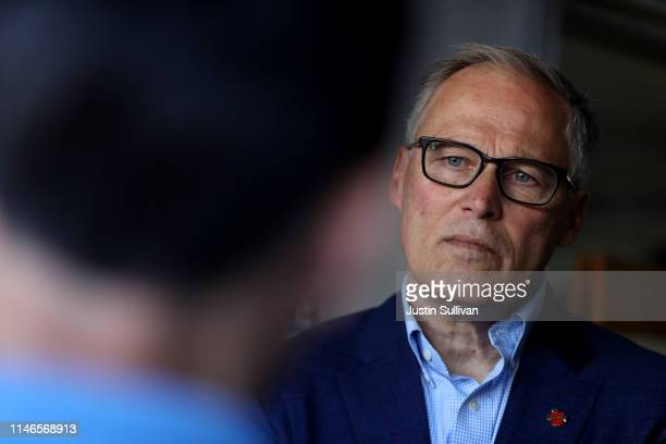 Democratic presidential candidate Washington Gov Jay Inslee looks on as he talks with solar workers at a home where they recently installed solar...