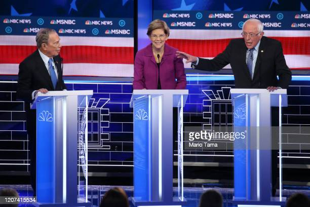 Democratic presidential candidates former New York City mayor Mike Bloomberg and Sen Elizabeth Warren listen as Sen Bernie Sanders makes a point...