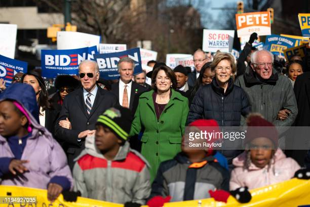 Democratic presidential candidates former Vice President Joe Biden left Sen Amy Klobuchar Sen Elizabeth Warren and Sen Bernie Sanders right march...