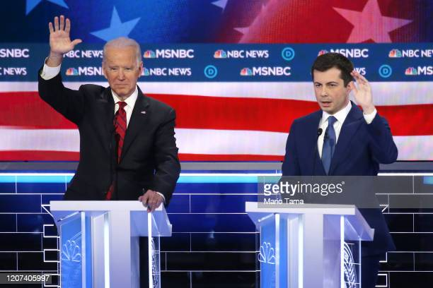 Democratic presidential candidates former Vice President Joe Biden and former South Bend, Indiana Mayor Pete Buttigieg raise their hands during the...