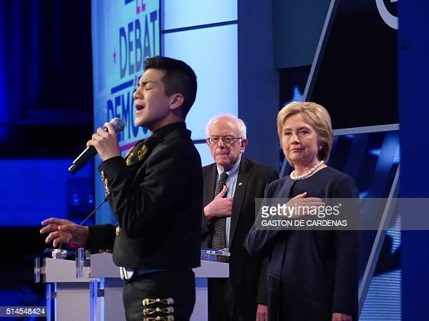 Democratic presidential candidates Hillary Clinton and Bernie Sanders stand during a National Anthem before the democratic presidential debate in...