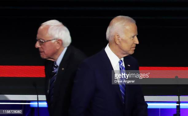 Democratic presidential candidates Sen Bernie Sanders and former Vice President Joe Biden pass each other on stage during the second night of the...
