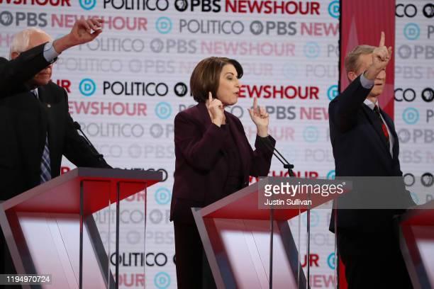 Democratic presidential candidates Sen Bernie Sanders and Tom Steyer raise their hands as Sen Amy Klobuchar speaks during the Democratic presidential...