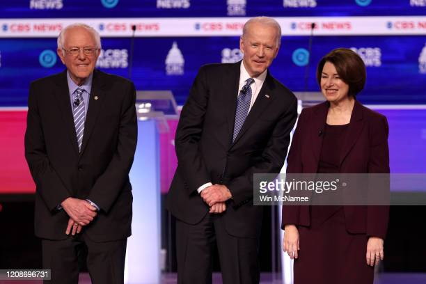 Democratic presidential candidates Sen Bernie Sanders former Vice President Joe Biden and Sen Amy Klobuchar walk on stage before the Democratic...
