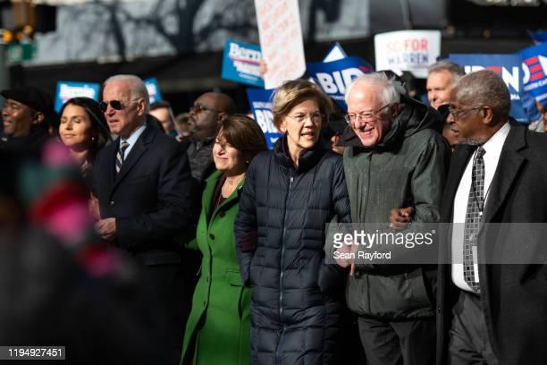 Democratic presidential candidates, Sen. Bernie Sanders , right, and Sen. Elizabeth Warren talk while marching with fellow presidential candidates...