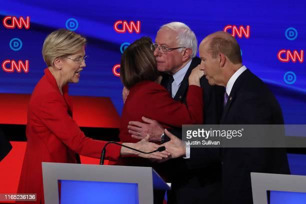 Democratic presidential candidates Sen Elizabeth Warren greets former Maryland congressman John Delaney while Sen Bernie Sanders hugs Sen Amy...