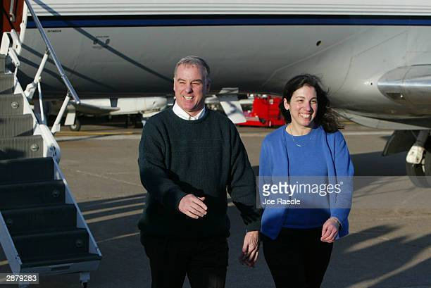 Democratic presidential hopeful and former Vermont Governor Howard Dean and his wife Judy Dean walk away from a plane after landing January 18 2004...