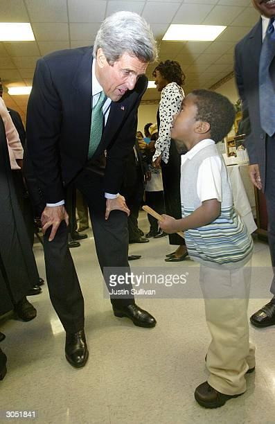 Democratic presidential hopeful and US Senator John Kerry greets a small child at the Greater Bethlehem Temple Apostolic Faith Church March 7 2004 in...