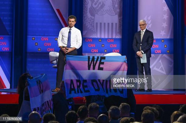TOPSHOT Democratic presidential hopeful Mayor of South Bend Indiana Pete Buttigieg flanked by moderator CNN's Anderson Cooper reacts as protesters...