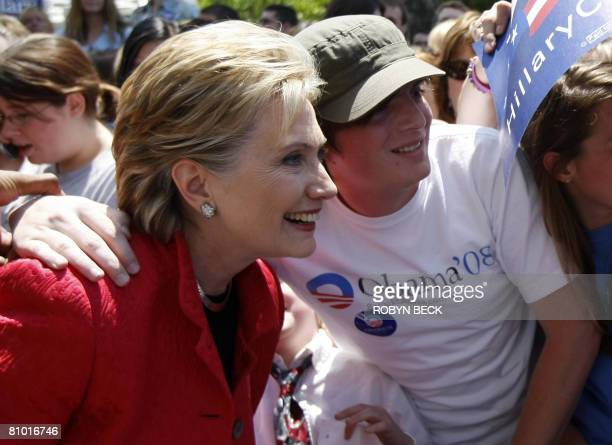 Democratic presidential hopeful New York Senator Hillary Rodham Clinton poses for a snapshot with a man wearing an Obama tee shirt at a campaign...