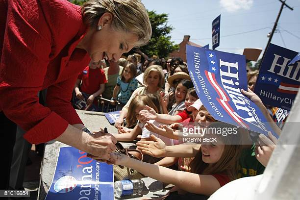 Democratic presidential hopeful New York Senator Hillary Rodham Clinton signs the hands of young girls at a campaign event outside McMurran Hall at...