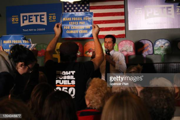 Democratic presidential hopeful Pete Buttigieg confronts climate activists at a pizzeria in Hampton New Hampshire the morning after the flawed Iowa...