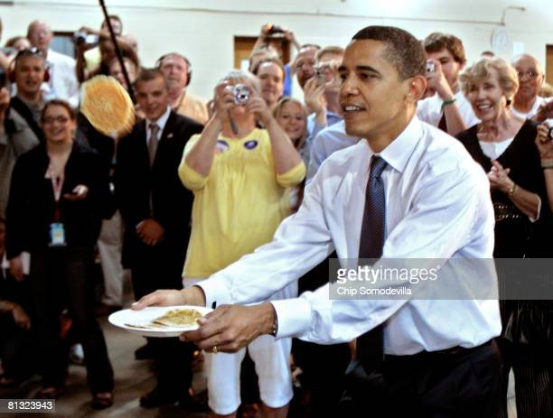 Democratic presidential hopeful Sen Barack Obama catches a pancake with his plate during a breakfast with veterans and military families in the...