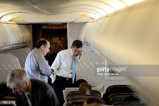 Democratic presidential hopeful Sen Barack Obama talks with his chief campaign strategist David Axelrod while flying from Chicago to Newark for the...