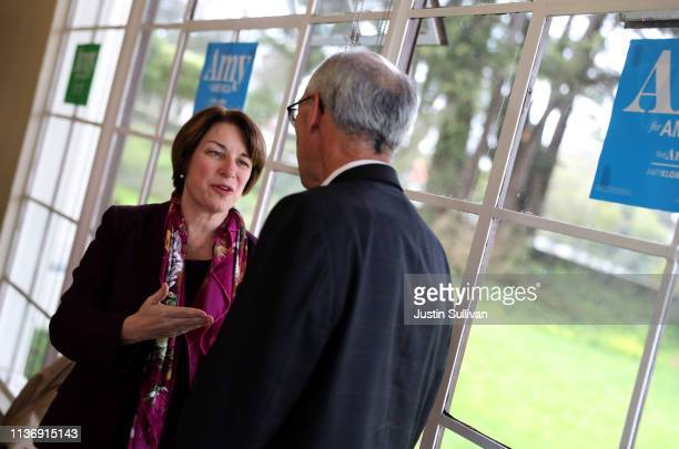 Democratic presidential hopeful US Sen Amy Klobuchar greets an attendee during a roundtable discussion on climate change on March 19 2019 in San...