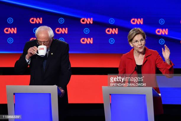 Democratic presidential hopeful US Senator from Massachusetts Elizabeth Warren speaks next to US senator from Vermont Bernie Sanders during the first...