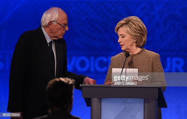US Democratic presidential hopefuls Bernie Sanders and Hillary Clinton confers during a break in the Democratic Presidential Debate hosted by ABC...