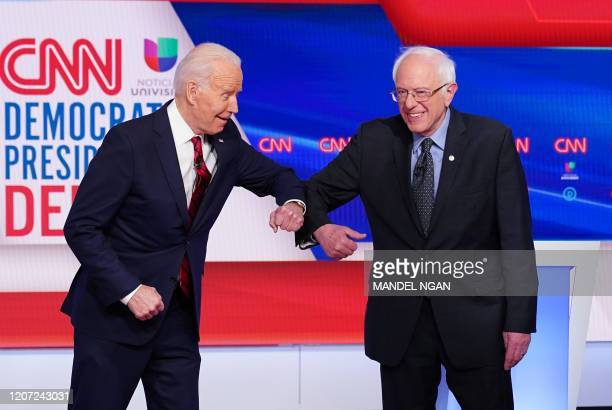 Democratic presidential hopefuls former US vice president Joe Biden and Senator Bernie Sanders greet each other with an elbow bump as they arrive for...
