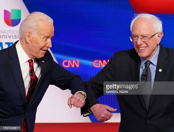 TOPSHOT Democratic presidential hopefuls former US vice president Joe Biden and Senator Bernie Sanders greet each other with a safe elbow bump before...