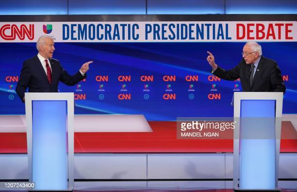 Democratic presidential hopefuls former US vice president Joe Biden and Senator Bernie Sanders point fingers at each other as they take part in the...