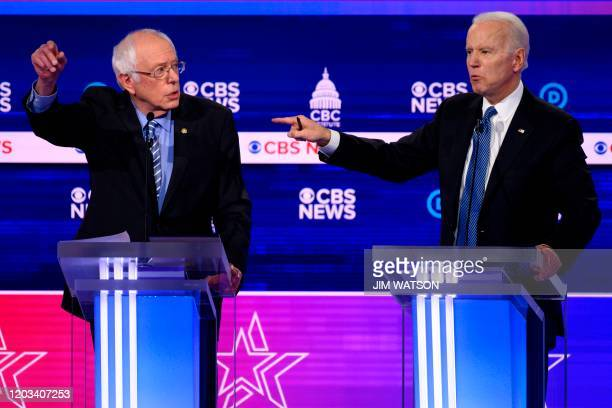 Democratic presidential hopefuls Vermont Senator Bernie Sanders and former Vice President Joe Biden gesture as they participate in the tenth...