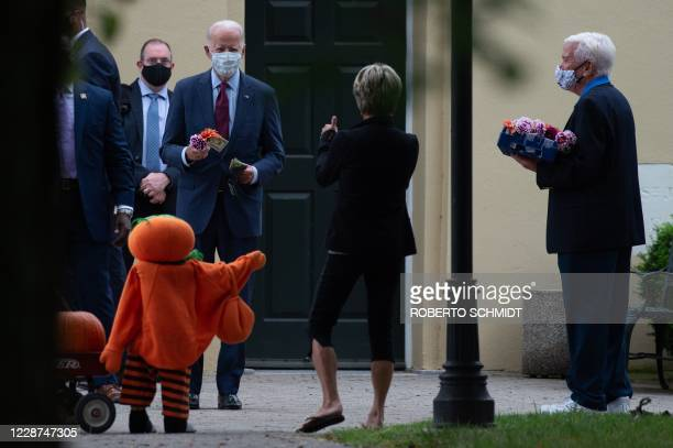 TOPSHOT Democratic presidential nominee and former Vice President Joe Biden buys a flower decoration from a woman in front of the St Joseph On the...