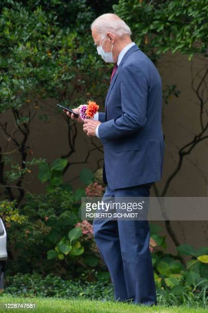 Democratic presidential nominee and former Vice President Joe Biden looks at this phone while holding a flower decoration he purchased as he left the...