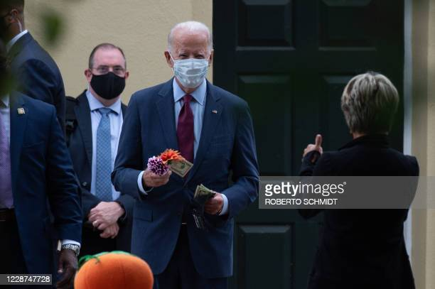 Democratic presidential nominee and former Vice President Joe Biden buys a flower decoration from a woman in front of the St Joseph On the Brandywine...