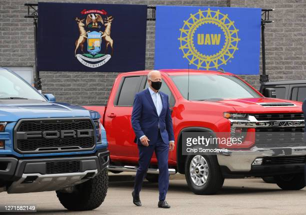 Democratic presidential nominee and former Vice President Joe Biden walks out in between pickup trucks before delivering remarks in the parking lot...