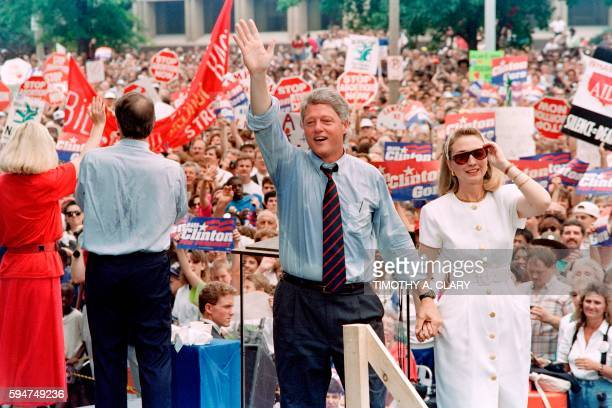 Democratic Presidential nominee Bill Clinton waves as he holds his wife Hillary's hand after speaking on July 22 1992 to a rally estimated at 40000...