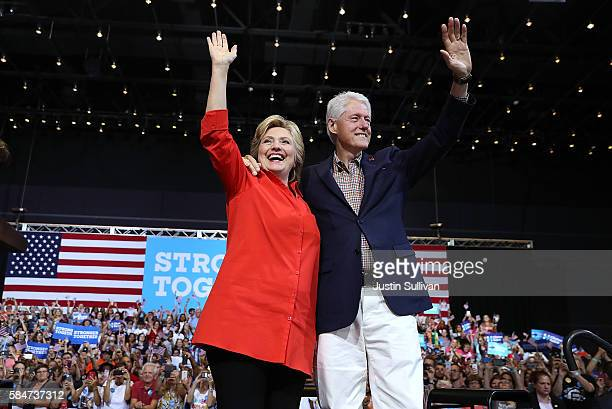 Democratic presidential nominee former Secretary of State Hillary Clinton and her husband former US president Bill Clinton greet supporters during a...