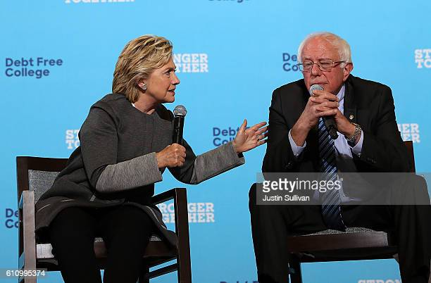 Democratic presidential nominee former Secretary of State Hillary Clinton speaks as US Sen Bernie Sanders looks on during a campaign rally at...