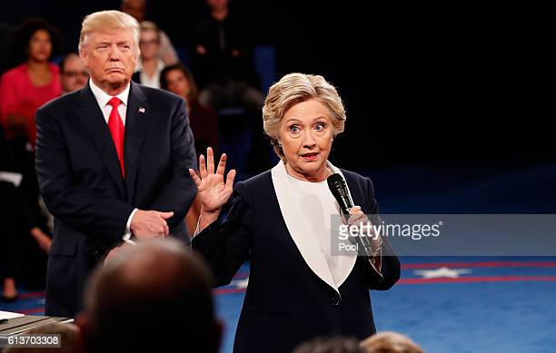Democratic presidential nominee former Secretary of State Hillary Clinton speaks as Republican presidential nominee Donald Trump listens during the...