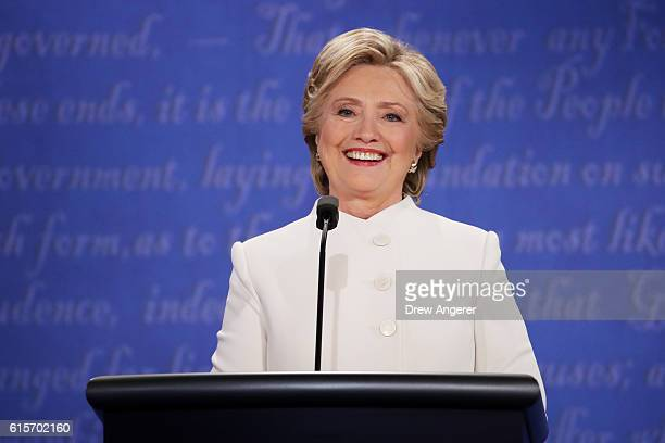 Democratic presidential nominee former Secretary of State Hillary Clinton smilels as she listens to Republican presidential nominee Donald Trump...