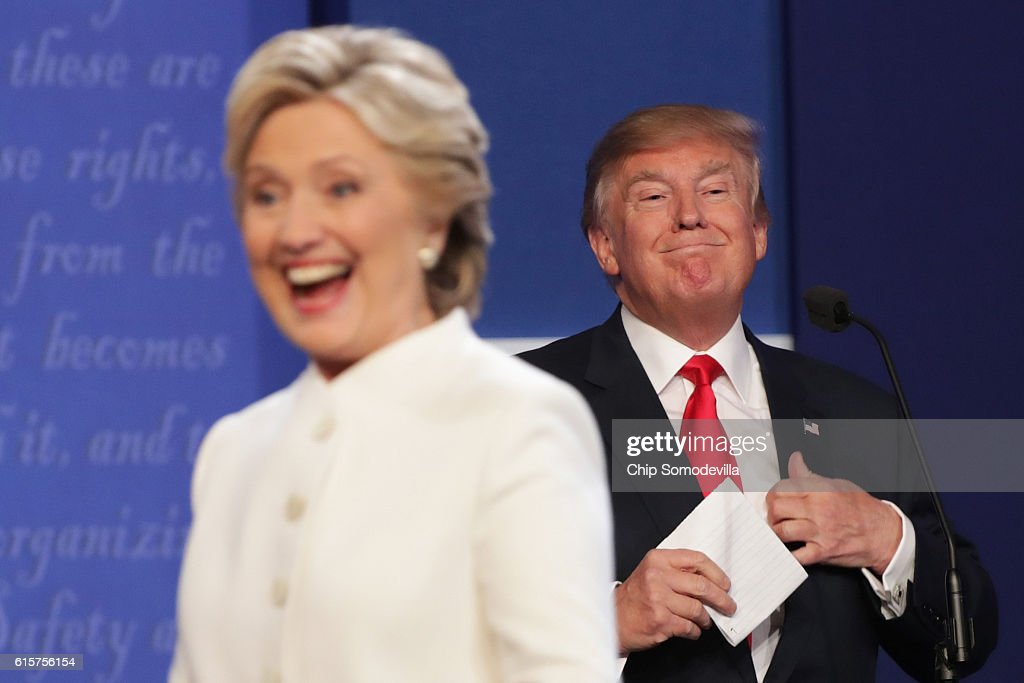 Democratic presidential nominee former Secretary of State Hillary Clinton walks off stage as Republican presidential nominee Donald Trump smiles after the third U.S. presidential debate at the Thomas & Mack Center on October 19, 2016 in Las Vegas, Nevada. Tonight is the final debate ahead of Election Day on November 8.