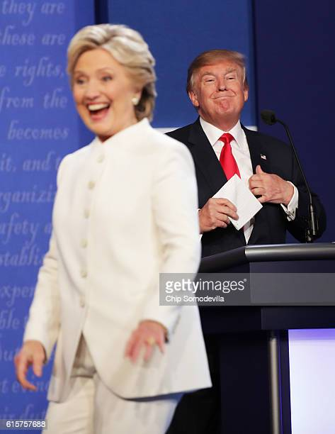 Democratic presidential nominee former Secretary of State Hillary Clinton walks off stage as Republican presidential nominee Donald Trump smiles...