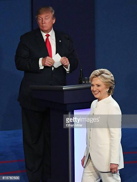 Democratic presidential nominee former Secretary of State Hillary Clinton walks off stage as Republican presidential nominee Donald Trump looks on at...