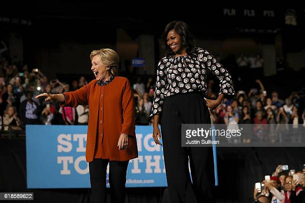 Democratic presidential nominee former Secretary of State Hillary Clinton and First Lady Michelle Obama greet supporters during a campaign rally at...