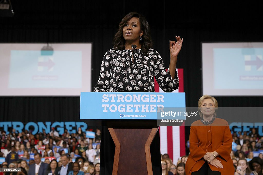 Democratic presidential nominee former Secretary of State Hillary Clinton (R) looks on as First Lady Michelle Obama speaks during a campaign rally at Wake Forest University on October 27, 2016 in Winston-Salem, North Carolina. With less than two weeks to go before the election, Hillary Clinton is campaigning in North Carolina with First Lady Michelle Obama.