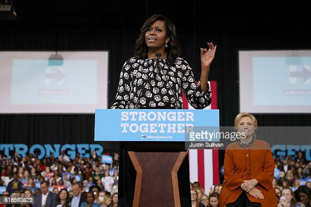 Democratic presidential nominee former Secretary of State Hillary Clinton looks on as First Lady Michelle Obama speaks during a campaign rally at...