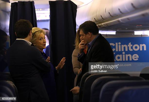 Democratic presidential nominee former Secretary of State Hillary Clinton talks with campaign advisor Philippe Reines aboard her campaign plane at...