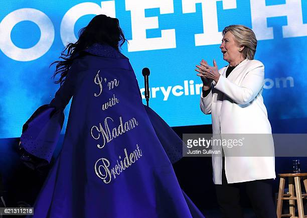 Democratic presidential nominee former Secretary of State Hillary Clinton looks at a cape worn by recording artist Katy Perry during a getoutthevote...